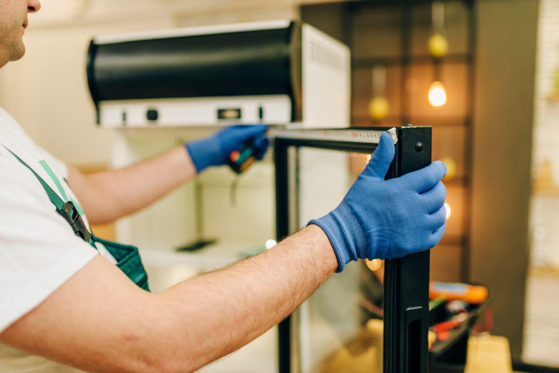 Monter naprawia ladę chłodniczą
