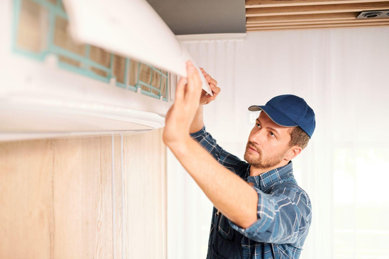Monter naprawia lub instaluje klimatyzator